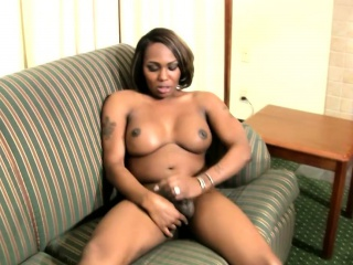 Horny TS gets her black skin covered in lotion and wanks off