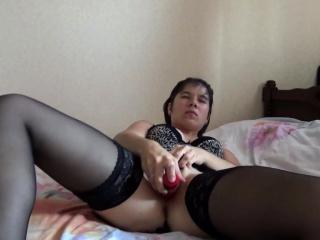 MILF wearing black stockings masturbates with a dildo