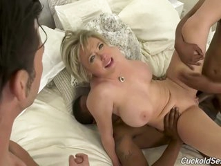 Busty blonde woman is sucking many hard cocks in a row in front of her husband